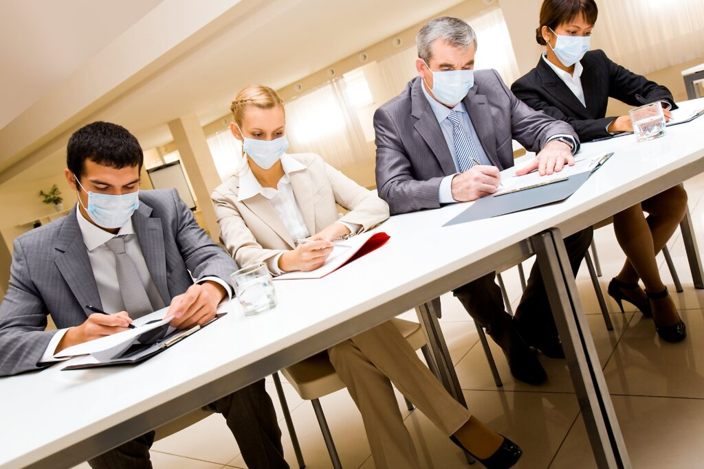 two men and two women business people wearing protective masks