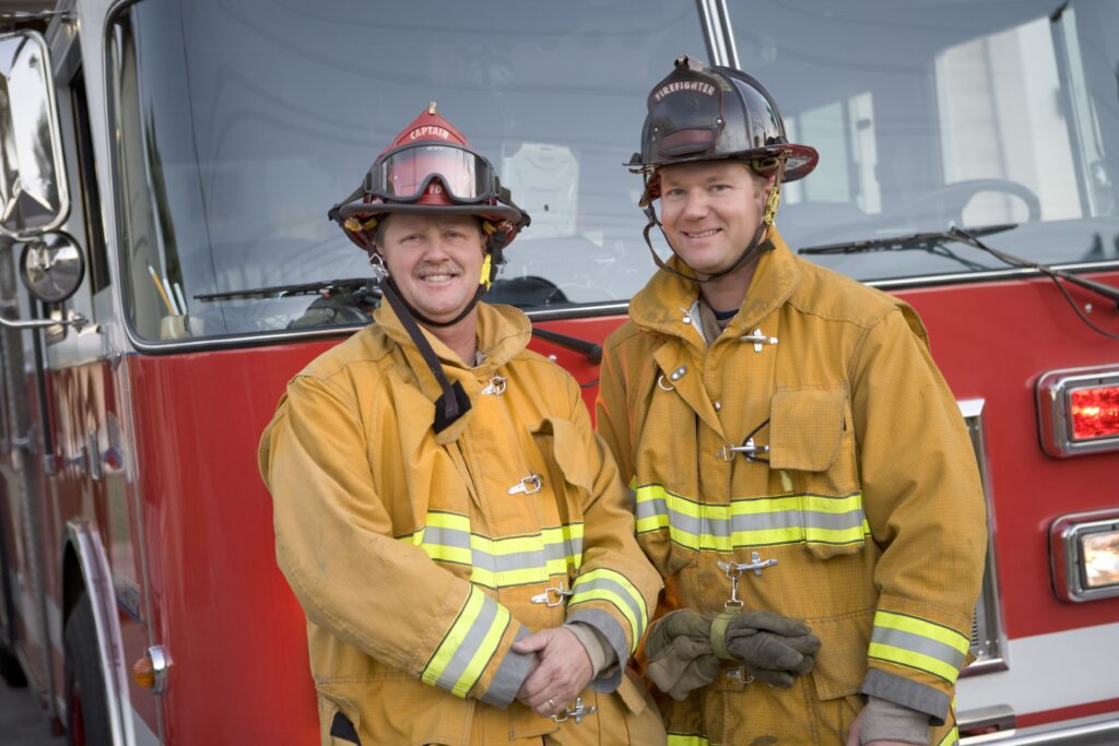 two male firefighters in front of red firetruck