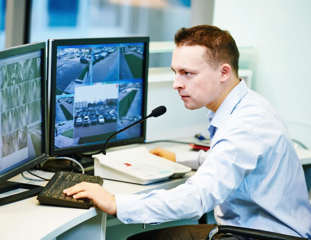 person sitting at central monitoring system with microphone